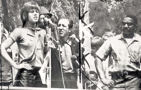 Braless Jane Fonda speaking at a rally