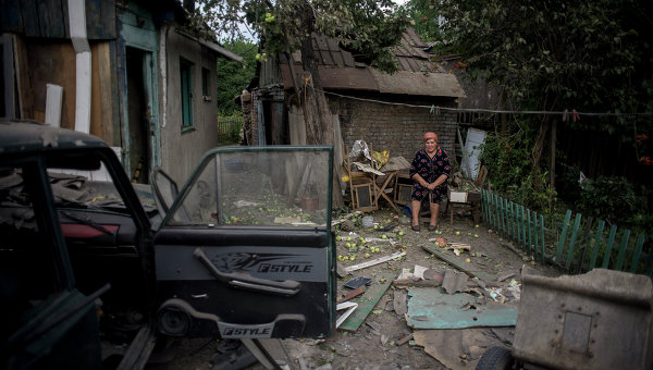 A old woman sits in the ruins of her area of Luhansk. Copyright © 2014 Rianovosti