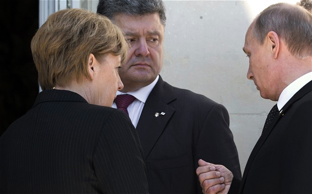 German chancellor Angela Merkel with Pietro Poroshenko and Valdimir Putin at the D-Day Anniversary in June. Copyright © 2014 Saul Loeb