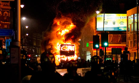 Police watching a burning bus, Tottenham, 6 August [Copyright © 2011 Leon Neal/AFP/Getty Images